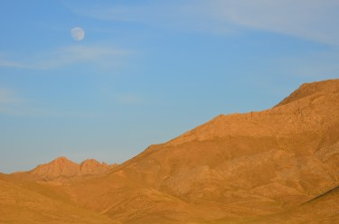 the full moon over the mountain at dusk