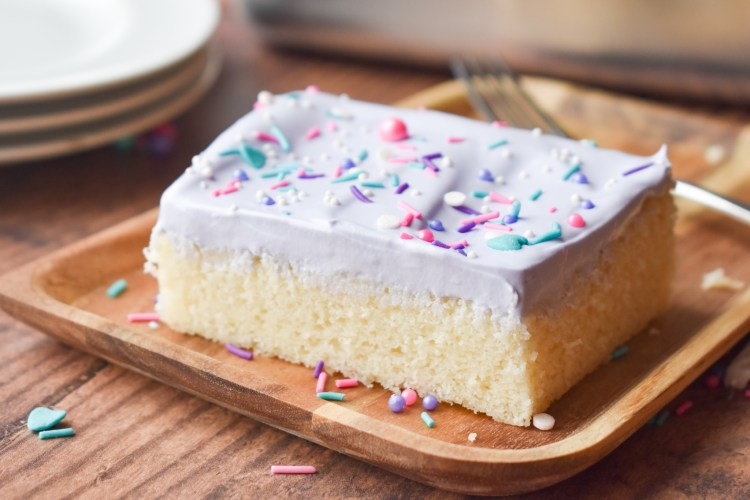 Cake with whipped cream frosting and sprinkles on a wooden board