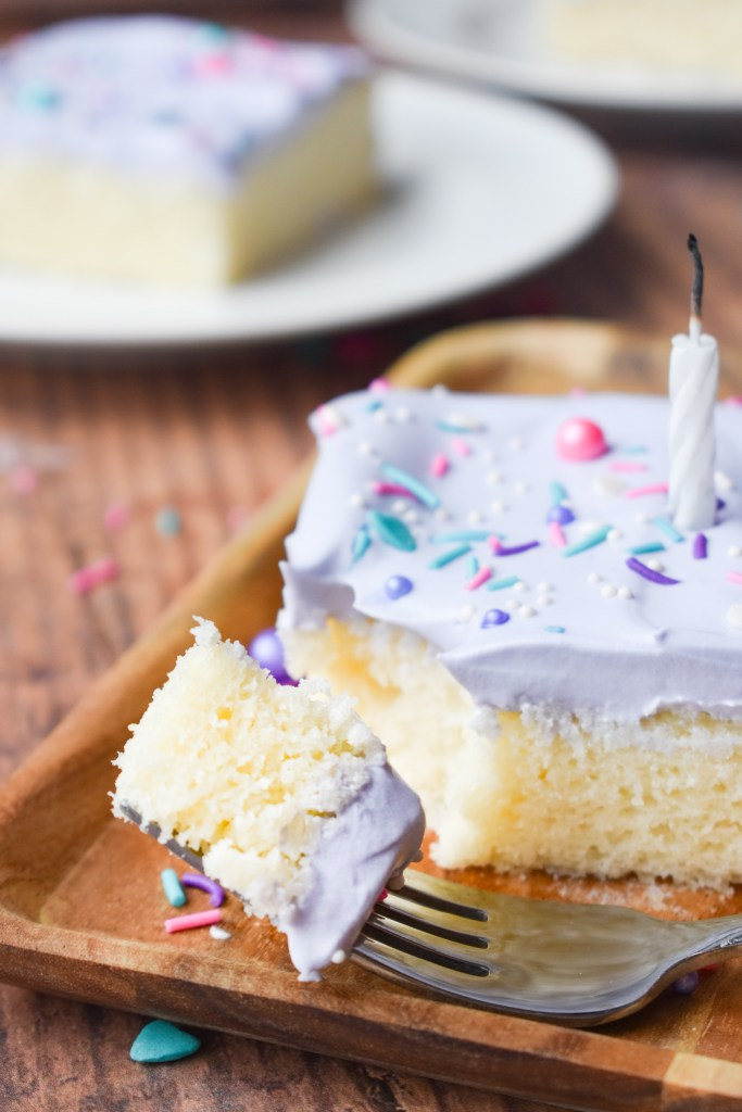 Cake with whipped cream frosting, sprinkles and a candle with fork grabbing a piece