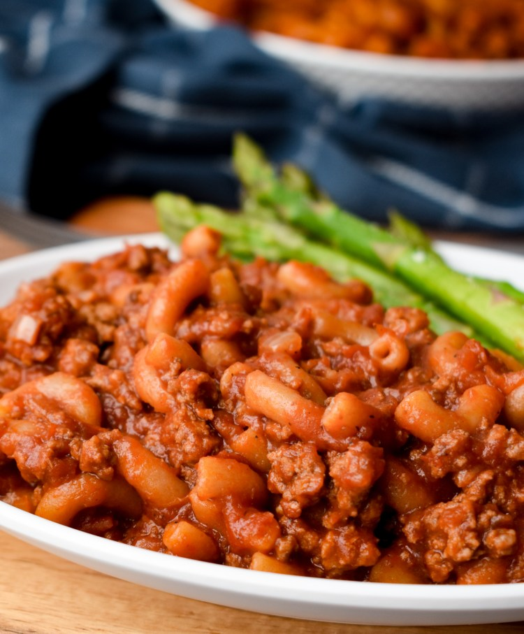 Beefaroni and asparagus on a white plate