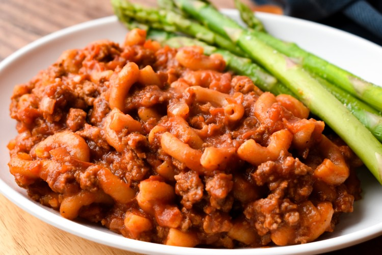White plate with homemade beefaroni and asparagus
