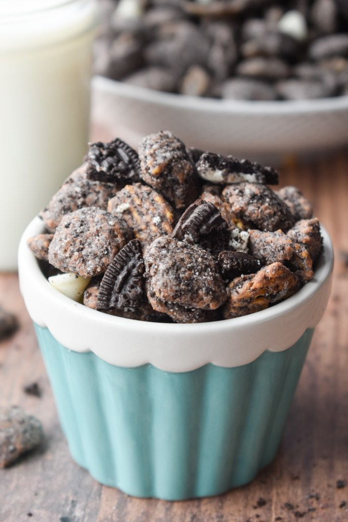Cookies and Cream Puppy Chow in a white and teal bowl with milk in the bakcground