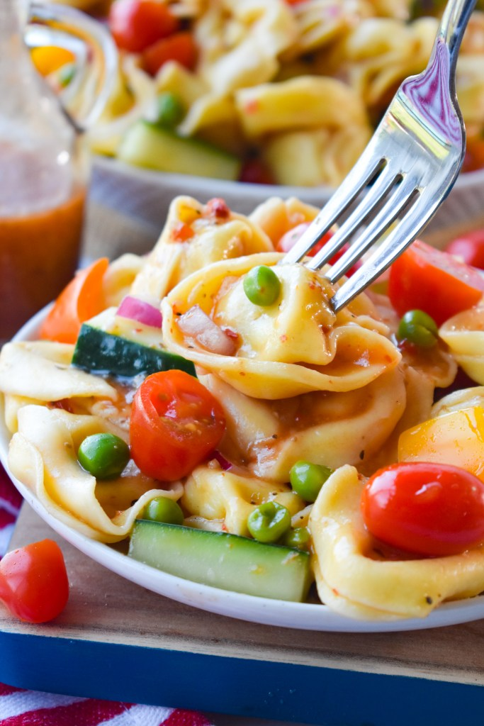 tortellini pasta salad with a fork going into a piece