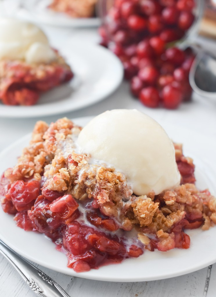 Scoop of cherry crisp on a white plate with vanilla ice cream and fresh cherries in the background