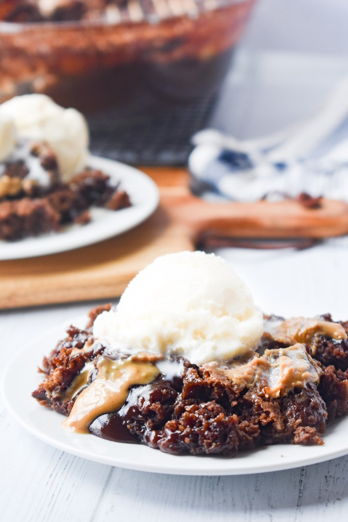 Chocolate Peanut Butter Cobbler on a white plate with ice cream on top
