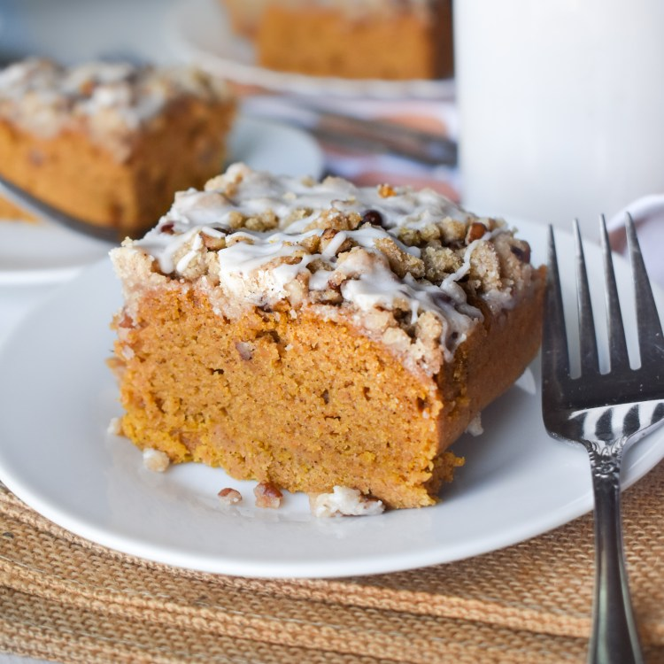 Slice of pumpkin coffee cake on a white plate and silver fork
