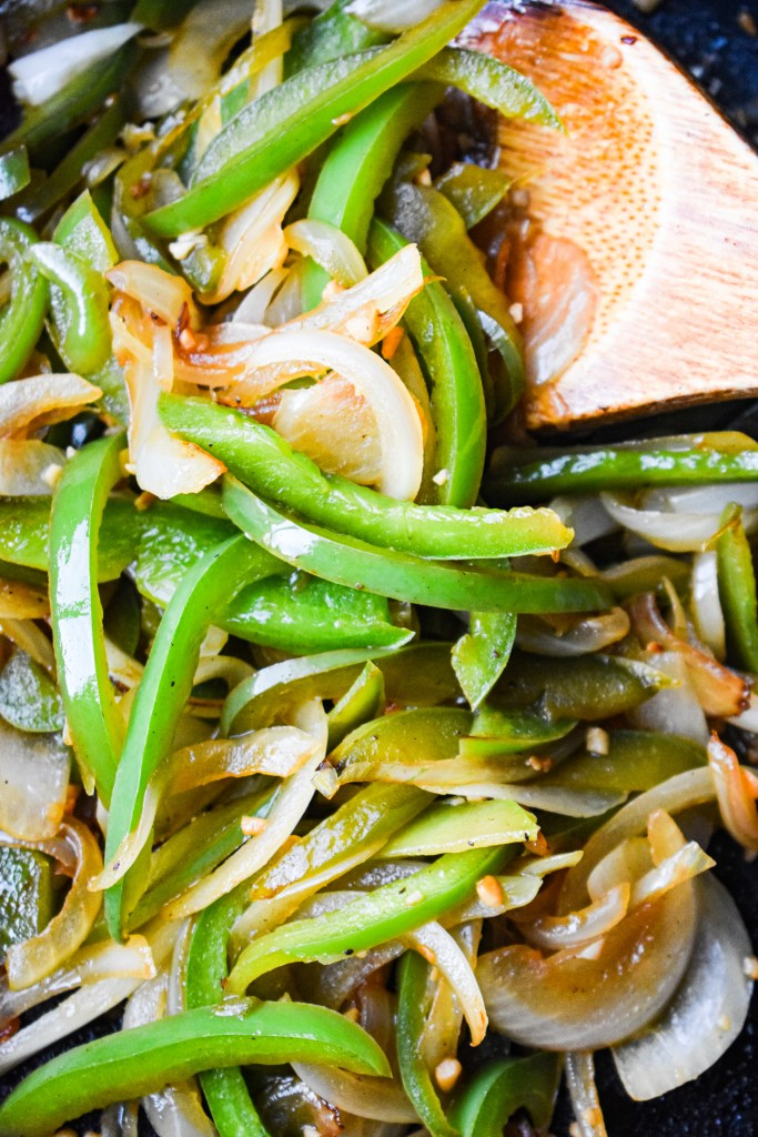 Green peppers and onions cooking in a pan.