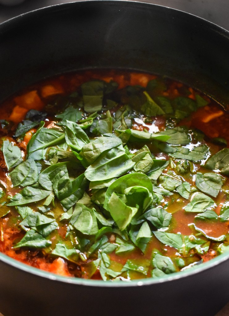 Pot of soup with spinach being added