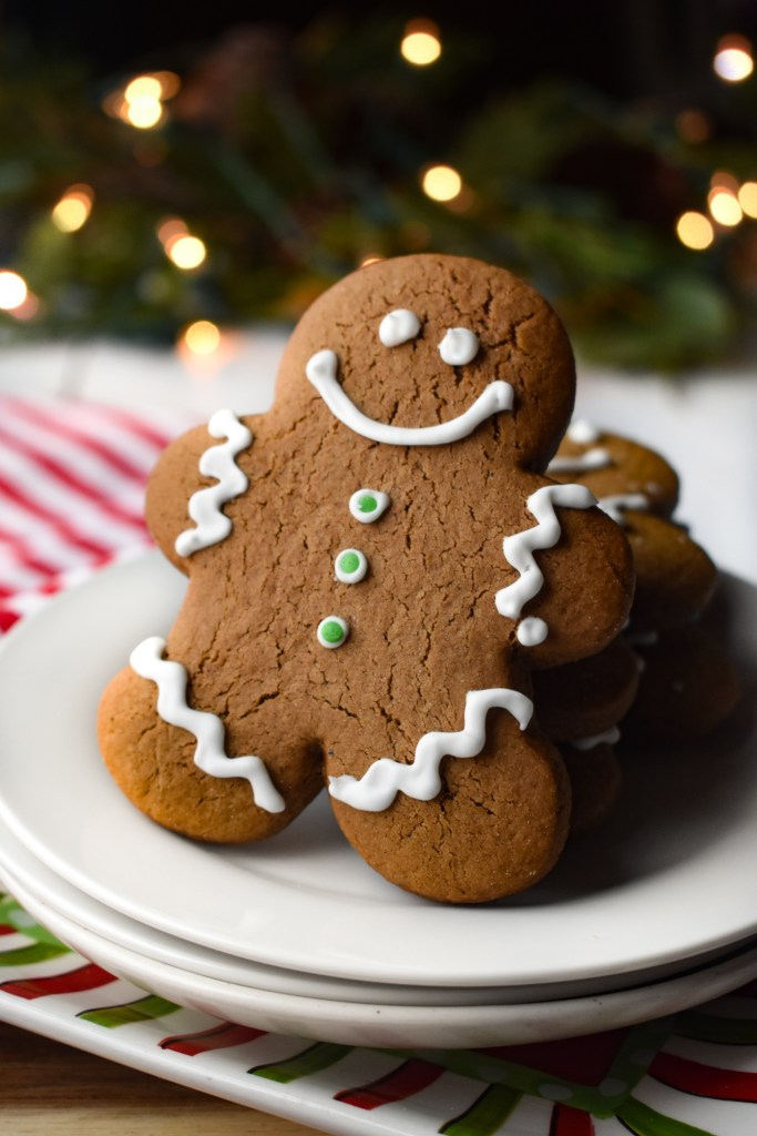 Gingerbread Cookies on a white plate with Christmas lights on in the background