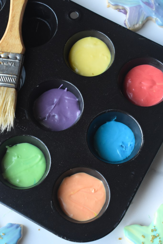 Muffin tin with colored frosting in the cups