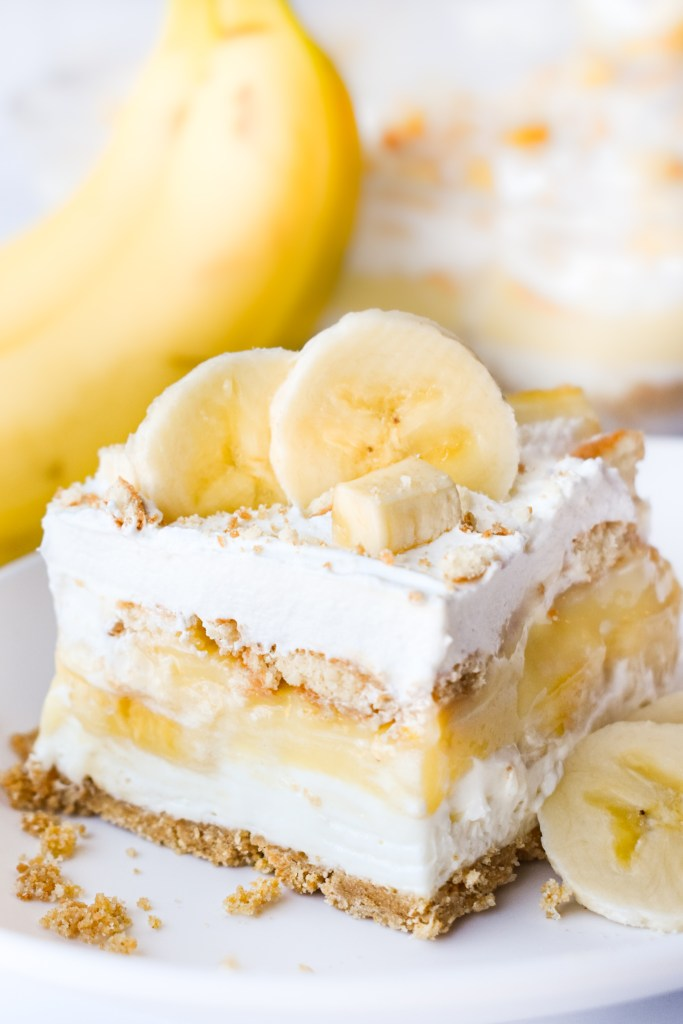 Banana Pudding Dessert on a plate with bananas in the background