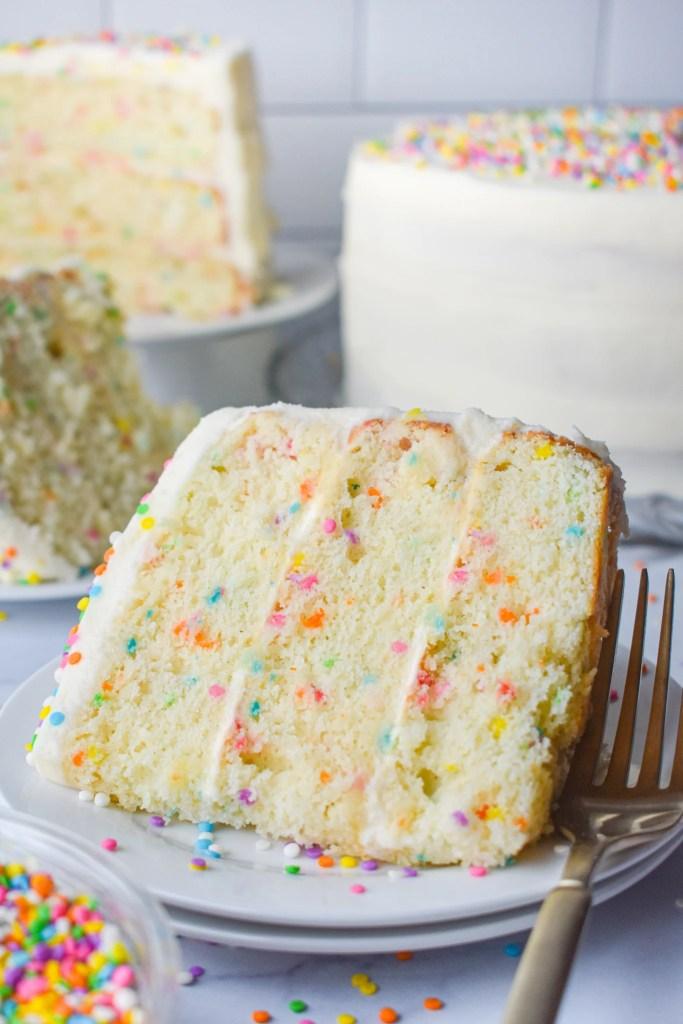 Slice of layered funfetti cake on a plate