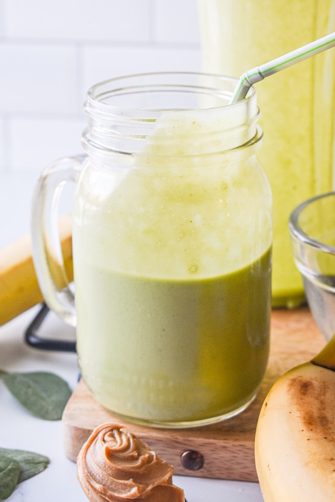 Green Monster Smoothie in a glass jar with a straw