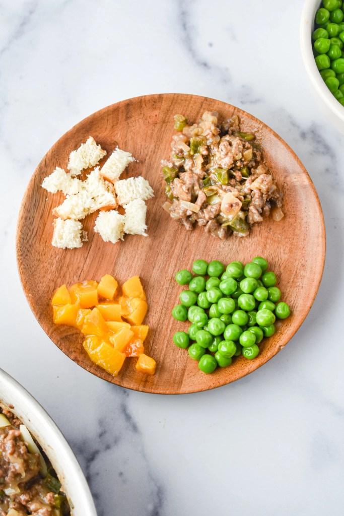 Healthy, balanced kids meal with sloppy joe meat, bun, peaches and peas