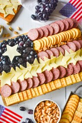 flag charcuterie board with crackers, cheese, grapes and flags around the board.