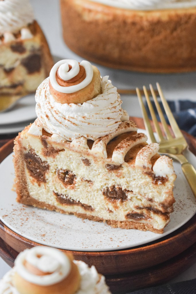 slice of cinnamon roll cheesecake on a white plate with a gold fork