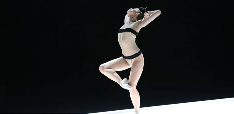 """Armitage Gone! female dancer in nude colored unitard with black band at chest and hip. Image is from """"You Took a Part of Me"""" performed at New York Live Arts."""