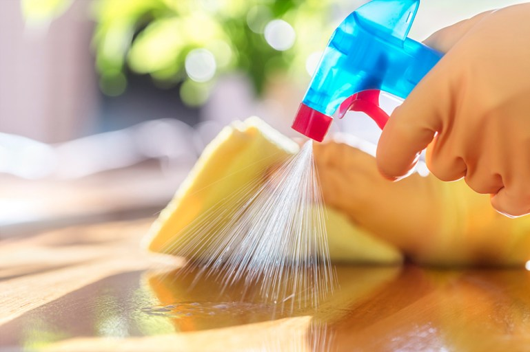 Cleaning with spray detergent, rubber gloves and dish cloth on work surface for hygiene