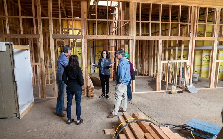 Workers and other people standing in a construction site, with wooden studs framing the space.
