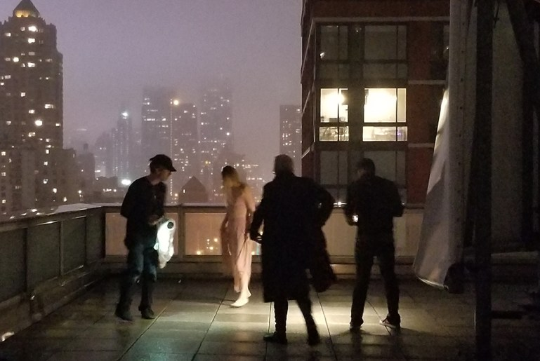 Dancer in pink, wearing Apolla socks, and photography crew, on a terrace doing a photo shoot with New York City skyscrapers in the background.