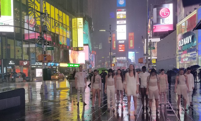 Dancers dressed in white, wearing Apolla Socks, in the rain with Times Square in the background.