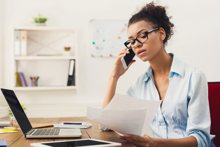 Businesswoman talking by phone with papers, sitting in modern home office.