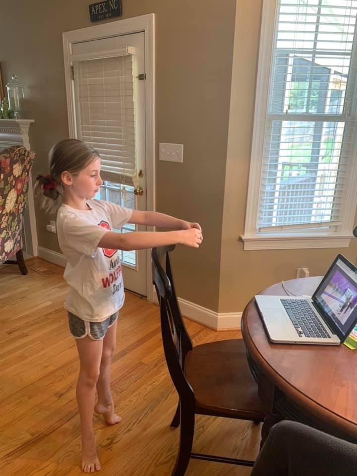 Young girl, in dance pose, facing a computer with an online dance class on screen.