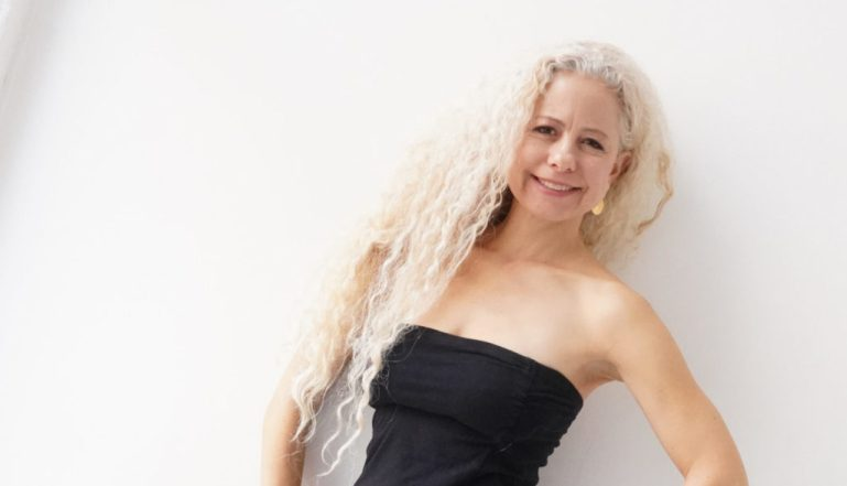 Valerie Green, executive director of Dance Entropy/Green Space, with long curly blond hair and strapless black dress.