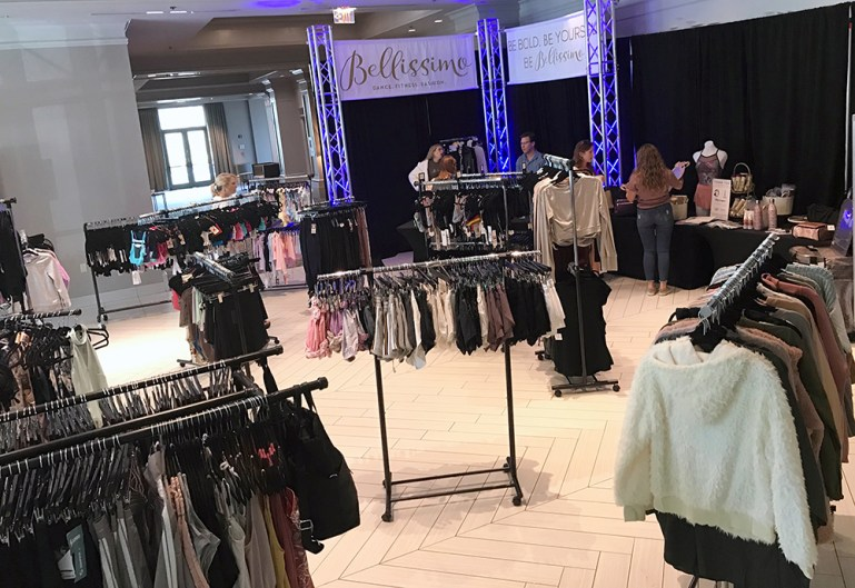 Pop-up store of Bellissimo Dance Boutique at its fashion show, with racks of tops, leotards, dance skirts.