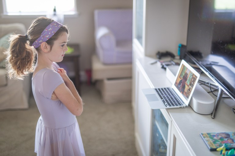 Young girl in dance dress looking at computer where dance class is being broadcast.