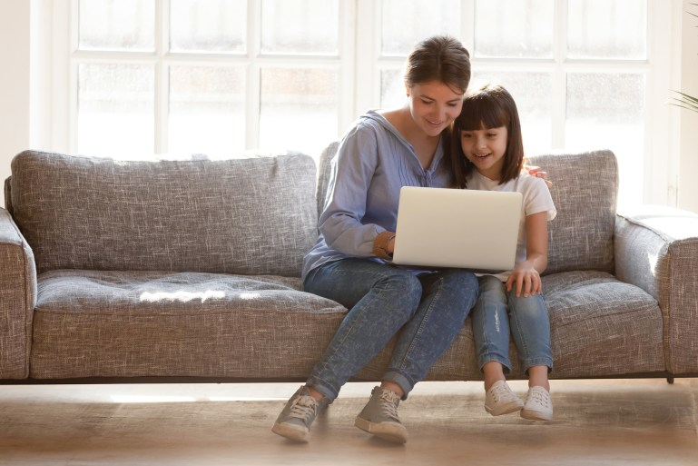 Mother and daughter sitting on couch in living room at home looking at a laptop computer together.