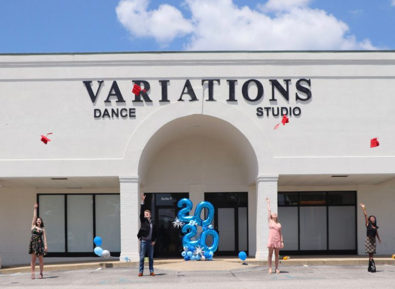 """Four seniors stand in the parking lot of Variations Dance Studio, spaced apart, throwing their graduation caps up into the air. A """"2020"""" balloon is behind them."""
