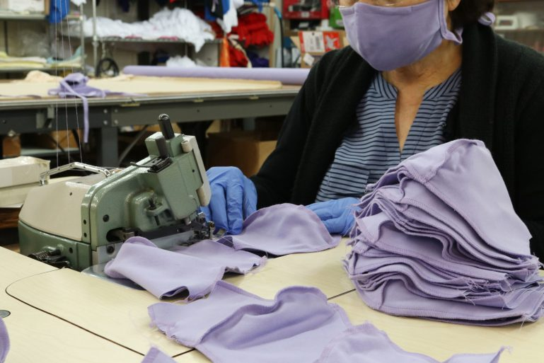 Eurotard employee at a sewing machine with a pile of purple masks she is making.