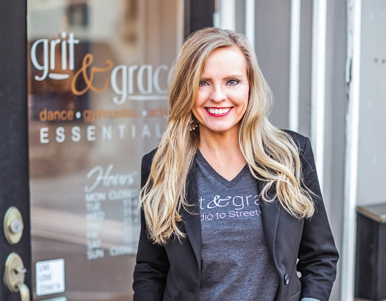 Stephanie Carney, a blonde woman in gray jacket and T-shirt, in front of the store she owns: Grit & Grace.