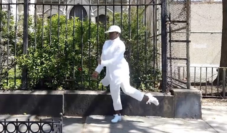 A screengrab of Boykin performing outside on a sidewalk, wearing an all-white outfit.