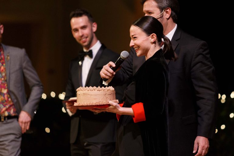 At a past gala, a Smuin dancer holds an iced chocolate cake in one hand and a microphone in the other, smiling.