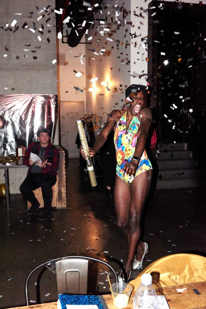 Raja wears an Andy Warhol leotard, and shouts in joy as silver confetti rains down around him.