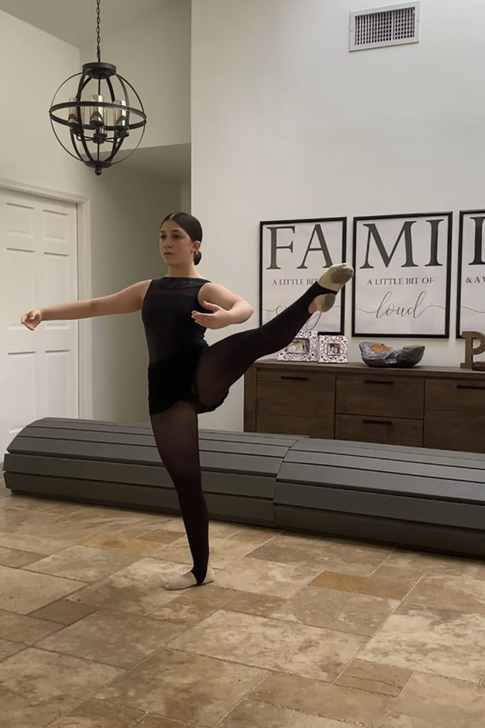 A teenage student takes class in her family's living room, in black ballet attire with leg extended to the side and arms in second position.