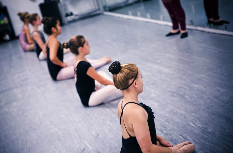 Five students sit on the floor of a dance studio in a straight line, wearing leotards and tights.