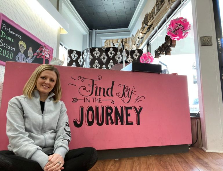 "Jennifer Velasquez sitting on floor cross-legged in front of the pink cash desk, which has the words ""find joy in the journey"" in script"