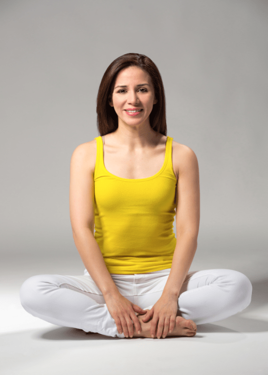 Zamarripa wears a bright yellow tank top and yellow pants and sits cross-legged on the ground, smiling at the camera.