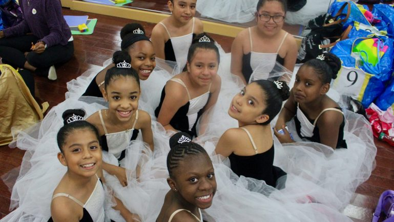A group of young girls sit on the floor and smile at the camera, wearing white tutus