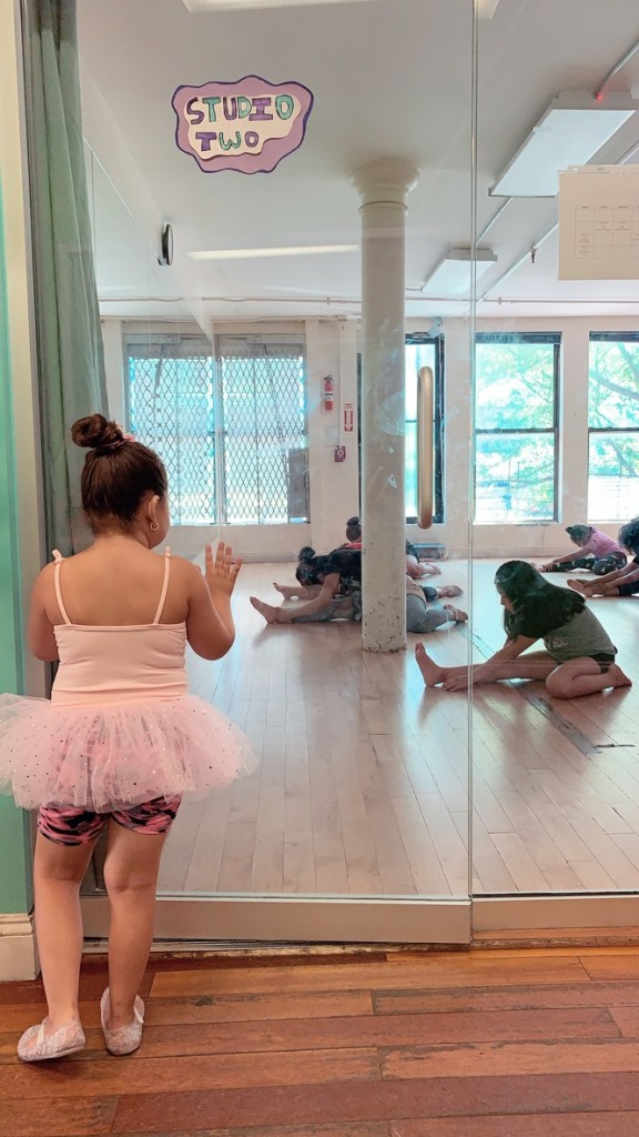 A young girl in a tutu looks through a glass door at a class in session, with students stretching on the floor