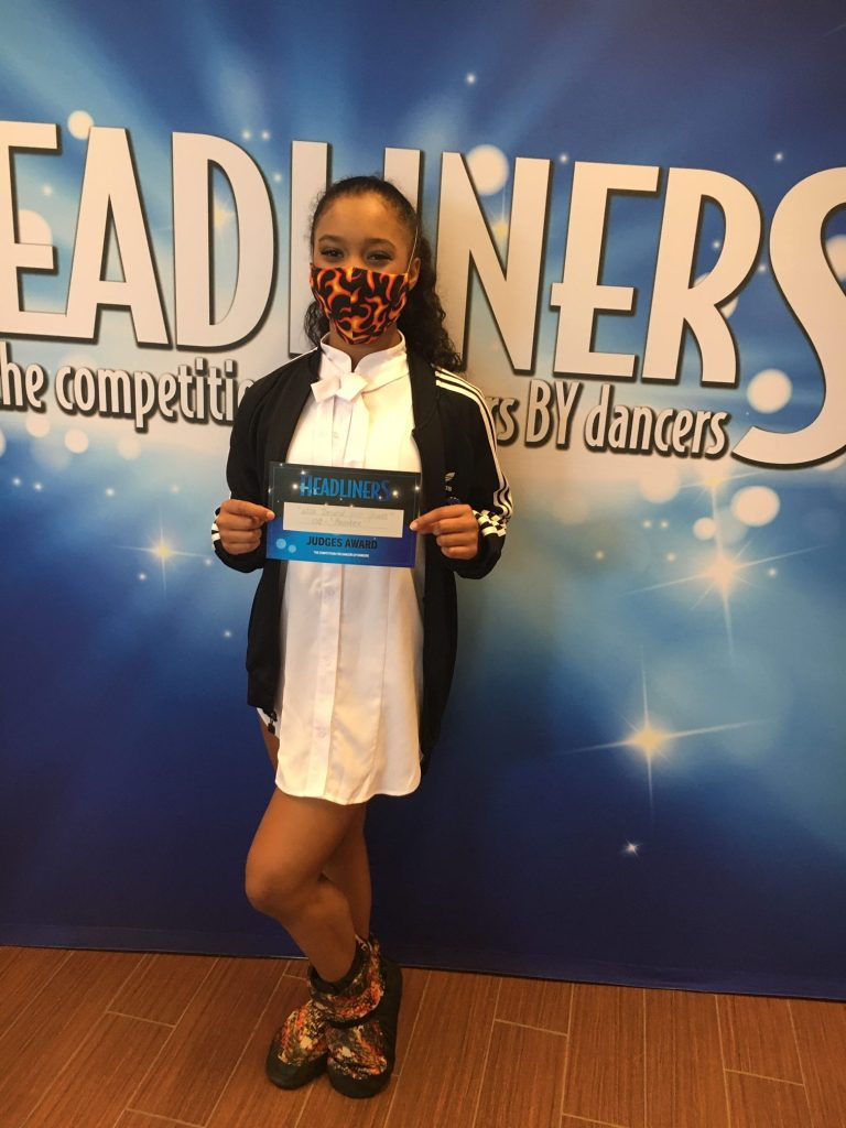 "A young masked dancer standing against a Headliners backdrop holds a certificate that says ""Headliners Judge's Award"""