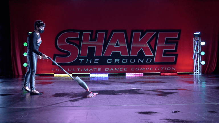 "A woman in a mask mops the stage. The big ""Shake the Ground"" logo is behind her on the stage's backdrop"