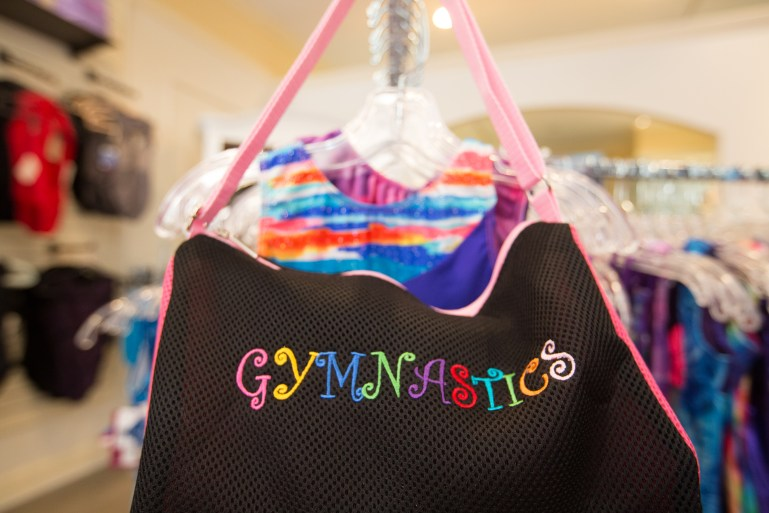 Black bag with embroidered letters spelling Gymnastics on it, and gymnastic leotards behind it.