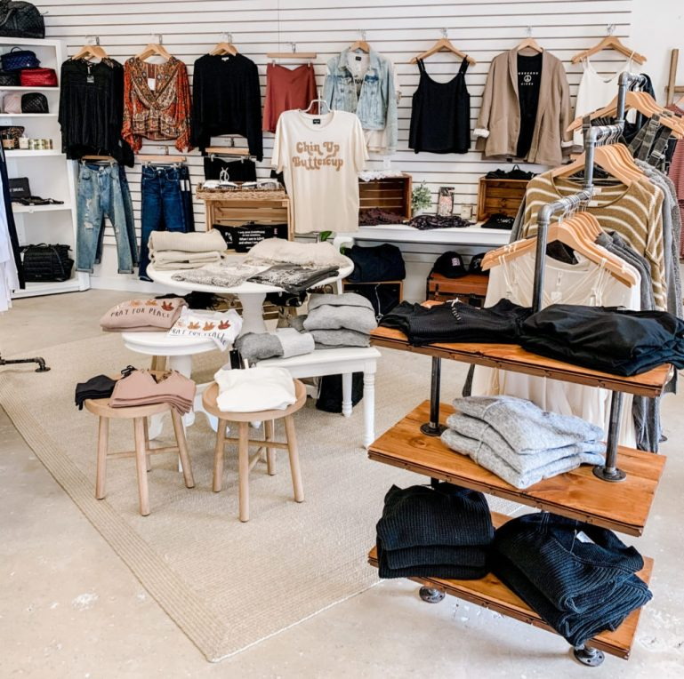 Display tables with women's fashion shirts and tops, with slat wall display of more fashion tops behind it.