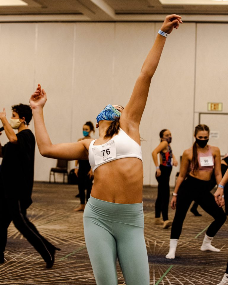 A teenage convention attendees wearing green pants, a white bra with her name and number on it and a blue patterned mask, leans back and reaches upwards. Other dancers improv around her