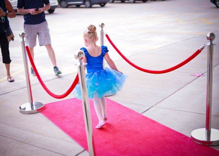 A young girl in a blue tutu costume walks down a red carpet in a parking lot