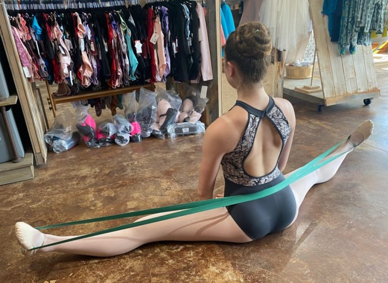 Dancer doing stretches with long band of elastic